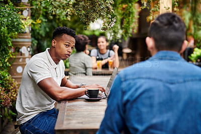 Buy stock photo Shot of two young men chatting in a restaurant