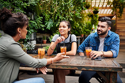 Buy stock photo Shot of a group of young friends chatting and having a drinks at a restaurant