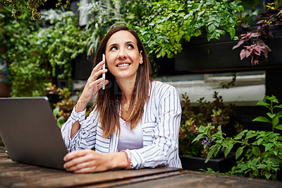 Buy stock photo Shot of a young woman using a smartphone and laptop at a restaurant
