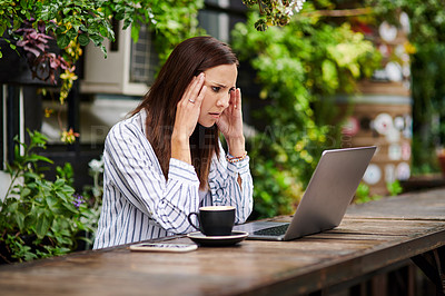 Buy stock photo Shot of a young woman looking stressed while using a laptop at a restaurant