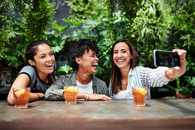 Buy stock photo Shot of a group of young women taking selfies while having drinks at a restaurant