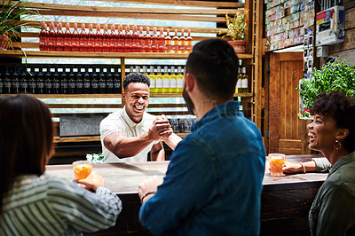 Buy stock photo Shot of a young bartender shaking hands with a customer at a bar