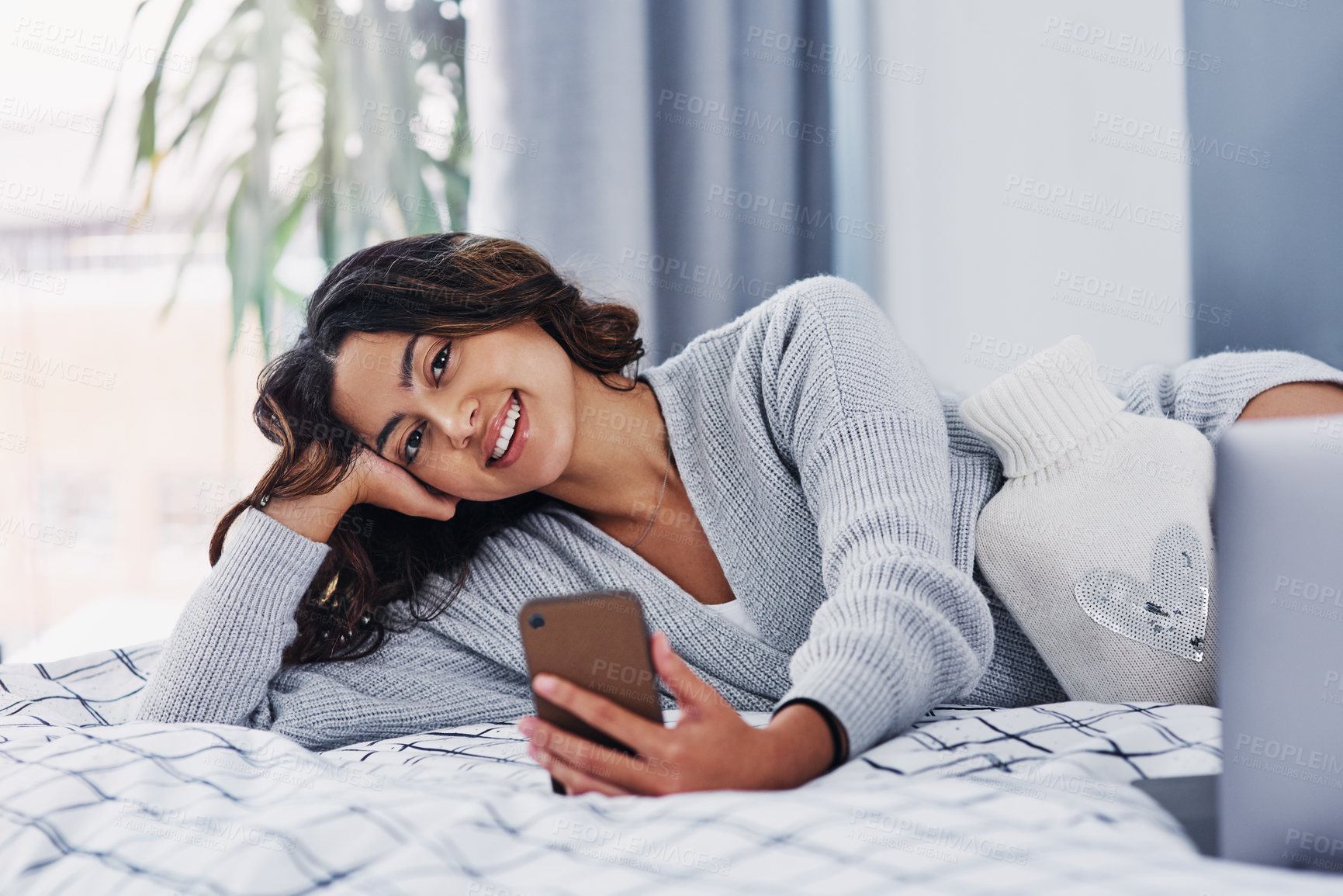 Buy stock photo Cropped portrait of an attractive young woman lying on her bed and using her cellphone while home alone