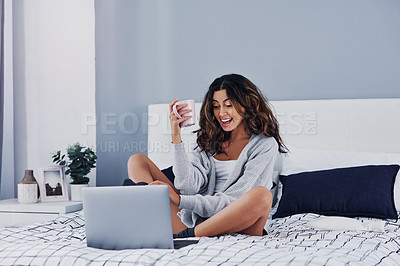Buy stock photo Full length shot of an attractive young woman sitting and enjoying a cup of coffee while using her laptop
