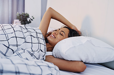 Buy stock photo Cropped shot of an attractive young woman waking up in her bed after sleeping in at home