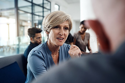 Buy stock photo Shot of a mature businesswoman having a conversation with a client inside a modern office with colleagues in the background