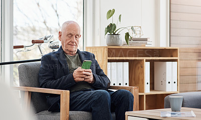 Buy stock photo Shot of a senior businessman using a cellphone in an office