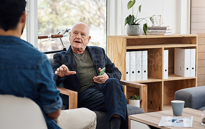 Buy stock photo Shot of a senior businessman having a discussion with a colleague in an office