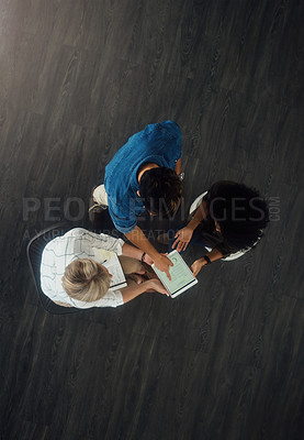 Buy stock photo High angle shot of a group of businesspeople working together on a digital tablet in an office