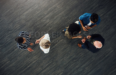 Buy stock photo High angle shot of a group of businesspeople talking to each other while standing in an office