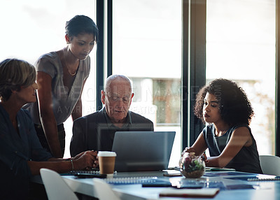 Buy stock photo Shot of a group of businesspeople using a laptop during their meeting at work