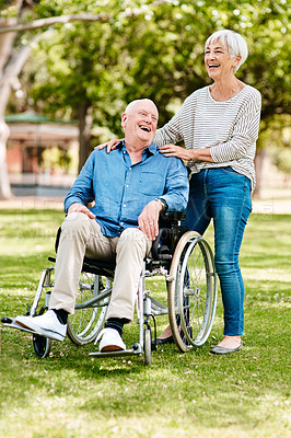 Buy stock photo Shot of a senior man sitting in a wheelchair while spending time outdoors with his wife