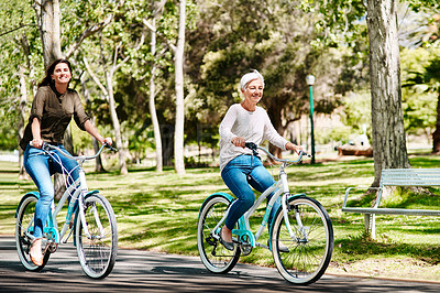 Buy stock photo Shot of a young woman and her senior mother out cycling through a park