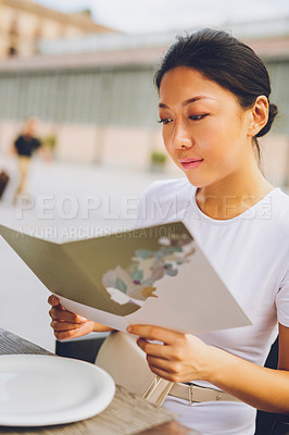 Buy stock photo Cropped shot of an attractive young woman sitting alone and reading a menu while at a restaurant on vacation