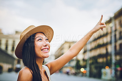 Buy stock photo Cropped shot of an attractive young woman standing alone and pointing at a building during a vacation in Spain