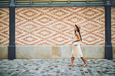 Buy stock photo Cropped shot of an attractive young woman walking along a wall during a vacation in Spain