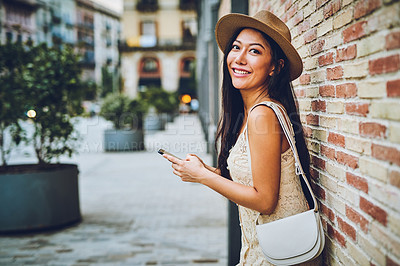 Buy stock photo Cropped shot of an attractive young woman standing against a wall and using her cellphone during a vacation