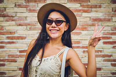 Buy stock photo Cropped shot of an attractive young woman standing against a wall and feeling playful while making a peace sign gesture
