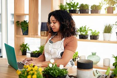 Buy stock photo Cropped shot of an attractive young female botanist working on a laptop in her florist