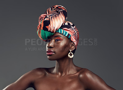 Buy stock photo Studio shot of a beautiful young woman wearing a traditional African head wrap against a grey background