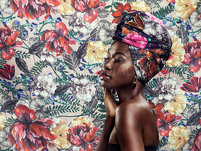Buy stock photo Studio shot of a beautiful young woman wearing a traditional African head wrap against a floral background