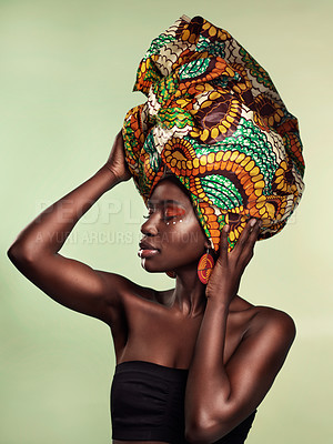 Buy stock photo Studio shot of a beautiful young woman wearing a traditional African head wrap against a green background