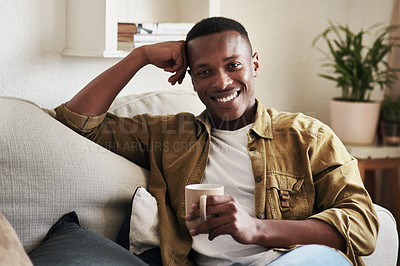 Buy stock photo Cropped portrait of a handsome young man smiling while having coffee on his couch at home
