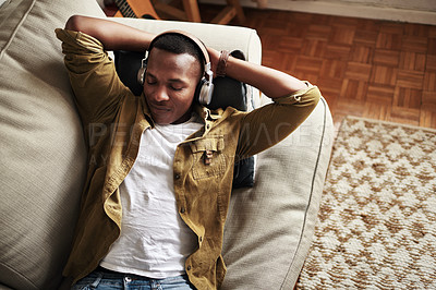 Buy stock photo High angle shot of a handsome young man listening to music on his headphones while lying on the couch at home