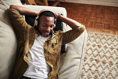 Buy stock photo High angle shot of a handsome young man smiling with his eyes closed while listening to music on his headphones at home