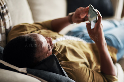 Buy stock photo Cropped shot of a handsome young man using a smartphone while relaxing on his couch at home