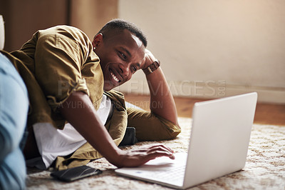 Buy stock photo Cropped shot of a handsome young man smiling while using a laptop in his living room at home