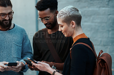 Buy stock photo Shot of a group of young creative businesspeople using their cellphones outside in the city
