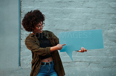 Buy stock photo Shot of an attractive young businesswoman holding a speech bubble outdoors in the city
