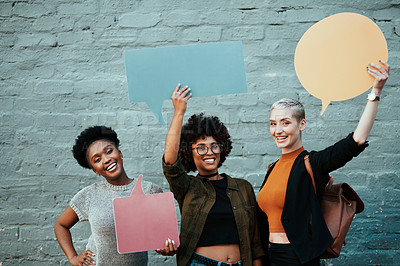 Buy stock photo Portrait of a group of young creative businesswomen holding up speech bubbles while posing together outside in the city
