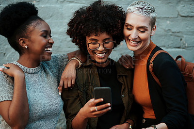 Buy stock photo Shot of a group of attractive young creative businesswomen using a cellphone together outside in the city