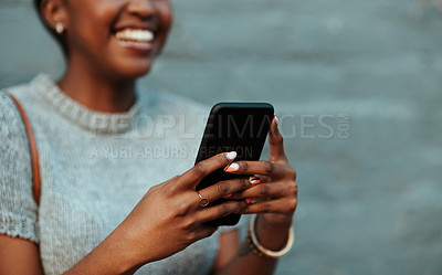 Buy stock photo Cropped shot of an unrecognizable young creative businesswoman using a cellphone outside in the city