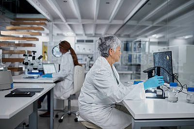 Buy stock photo Cropped shot of an attractive mature female scientist using a computer and a digital microscope in a laboratory with her colleague in the background