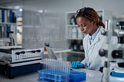 Buy stock photo Cropped shot of an attractive young female scientist using a laptop while working in a laboratory