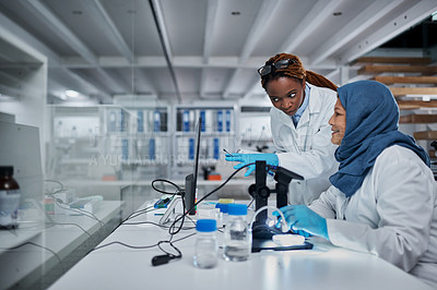 Buy stock photo Cropped shot of two female scientists having a discussion while using a computer and a digital microscope in a laboratory