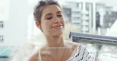 Buy stock photo Cropped shot of a young woman cleaning her windows at home