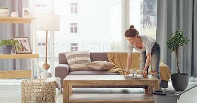 Buy stock photo Shot of a young woman cleaning her living room