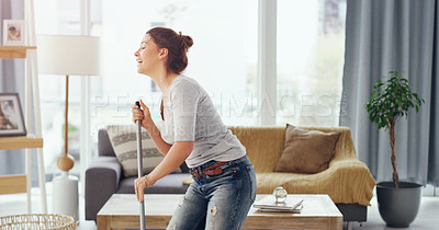 Buy stock photo Cropped shot of a young woman mopping the floor in her living room