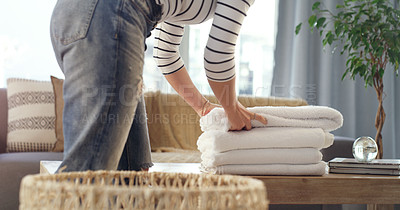 Buy stock photo Cropped shot of an unrecognizable woman folding up clean towels at home