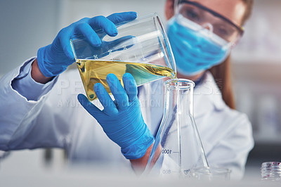 Buy stock photo Cropped shot of an unrecognizable female scientists wearing a protective face mask while mixing chemicals together inside of a laboratory
