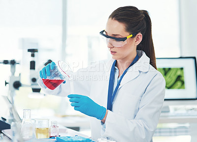 Buy stock photo Cropped shot of a focused young female scientist mixing chemicals together inside of a laboratory during the day