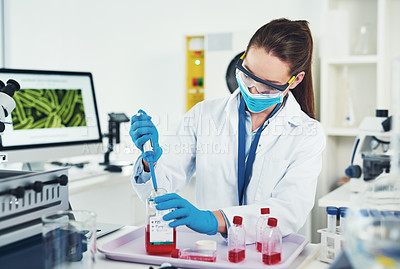 Buy stock photo Cropped shot of an unrecognizable young female scientist wearing protective fave gear while conducting experiments inside of a laboratory