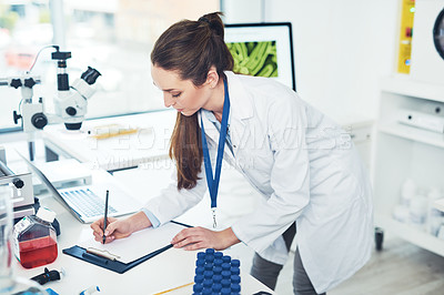 Buy stock photo Cropped shot of a focused young female scientist making notes in a book while doing tests inside of a laboratory during the day