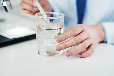 Buy stock photo Closeup of an unrecognizable scientist mixing chemicals together at their desk inside of a laboratory