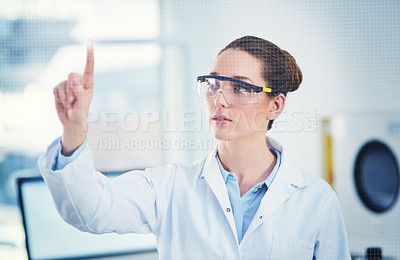Buy stock photo Cropped shot of a focused young female scientist wearing protective glasses while pointing with her finger on a glass wall