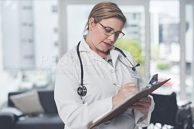 Buy stock photo Cropped shot of an attractive young female doctor writing on a clipboard while standing in her office